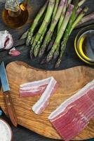 bereiding van Italiaans eenvoudig gerecht, asperges en spek foto