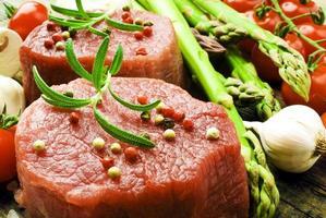 rauwe biefstuk met groene asperges op een houten bord foto