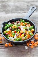 gemengde groenten maaltijd in oude koekenpan en ingrediënten foto