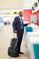 Afrikaanse zakenman door luchthaven inchecken balie foto