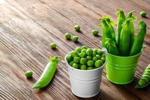 hartige verse groene erwten en peulen in een emmer op foto