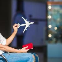 gelukkige vrouw met klein modelvliegtuig binnen luchthaven foto