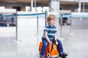kleine jongen gaat op vakantie reis met koffer op de luchthaven foto