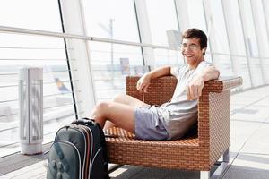 glimlachende mens die op vlucht op luchthaven wacht foto