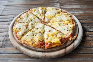 Hawaiiaanse pizza op houten tafel foto