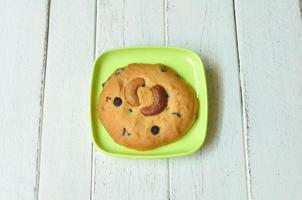 amandel-cookie en groene plaat op houten tafel. foto