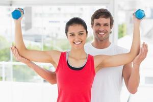 lachende instructeur met vrouw halter gewichten op te heffen foto