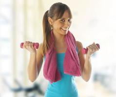 lachende fitness vrouw tillen gewichten op sportschool
