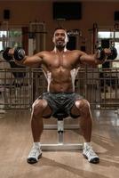 bodybuilder die schouders uitoefenen foto