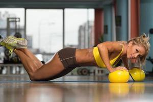 vrouw doet push-up oefening op gele ballen foto