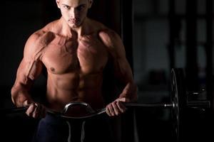 jonge man tillen een halter in het fitnesscentrum foto