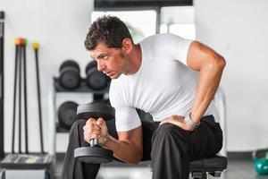 man tillen gewichten op sportschool