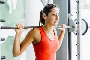 jonge mooie vrouw tillen gewichten in een sportschool