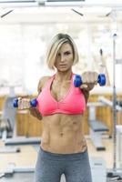 mooie vrouw Gewichtheffen in de sportschool op zoek foto