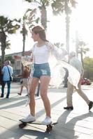 stijlvolle vrouw longboarder schaatsen op straat met plezier foto