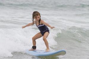 jong meisje surfen op surfplank foto