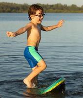 kleine jongen op rivier probeert te staan op het lichaam van bestuur