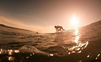 het meisje met surfen bij zonsopgang foto