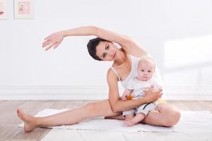 gezonde moeder en baby die gymnastiek maken foto