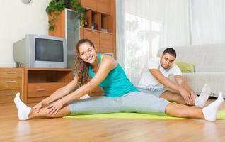 paar het beoefenen van yoga thuis foto