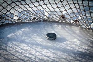 hockey puck in de achterkant van het net foto