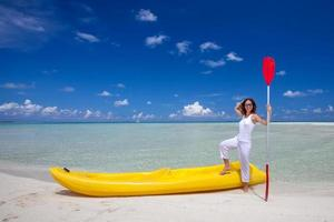 jonge blanke vrouw houdt peddel aan de kust foto