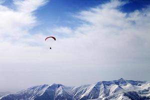 paraglider silhouet van bergen in winderige hemel foto