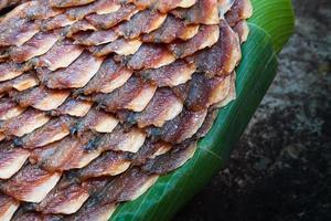 rij van gedroogde vis op bananenblad foto
