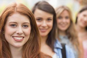gelukkige studenten die bij camera op een rij glimlachen foto