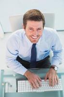 glimlachende zakenman die zijn computer met behulp van