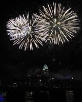 wit vuurwerk boven de skyline van cincinnati, drie uitbarstingen van verschillende groottes foto
