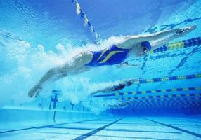 jonge vrouwelijke professionele deelnemers racen in zwembad foto