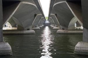 onder een betonnen brug met het water van de rivier. foto