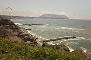 paragliden over de ruige kustlijn van Lima foto