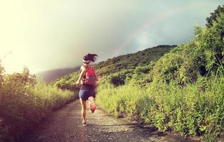 jonge fitness vrouw trail runner draait op zee berg foto