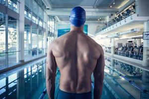 achteraanzicht van shirtless zwemmer bij het zwembad in het recreatiecentrum foto
