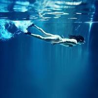 vrouwelijke duiker met masker en vinnen onder water foto