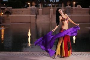 buikdanseres in rood kostuum danst met paarse sluier