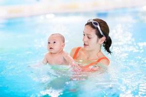 moeder en haar pasgeboren baby plezier in zwembad foto