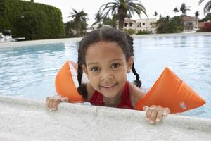 meisje ontspannen aan de rand van het zwembad foto