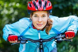 gelukkige jonge vrouw leunde over het stuur van haar fiets. foto