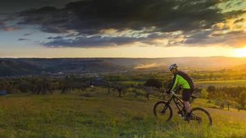 man op een mountainbike, zonsondergang foto