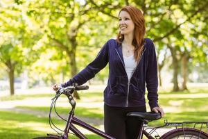 mooie roodharige met haar fiets foto