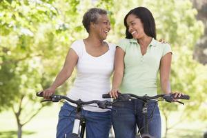 twee vrouwen op fietsen buitenshuis lachend