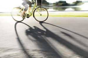 persoon op de fiets werpt schaduw foto