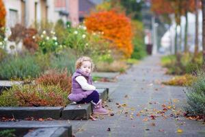 klein meisje in een herfst stad straat foto