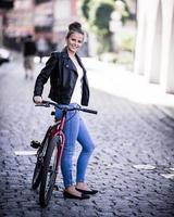 stedelijk fietsmeisje en fiets in stad foto