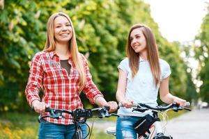 twee mooie meisjes in de buurt van fietsen