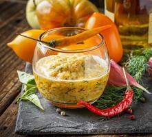 pittige pikante saus van gele zontomaten in een glas foto