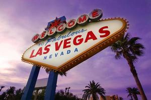 Las Vegas welkom bord met palmbomen bij zonsondergang foto